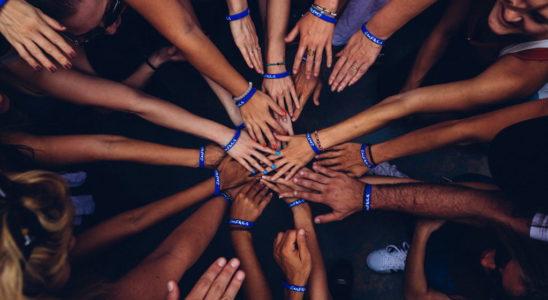 um grupo de pessoas em roda juntam as maos como uma equipe